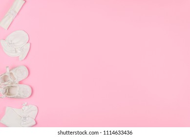 Top view of baby socks, gloves, hair band and booties for newborn on pink background. Copy space for text. Top view.