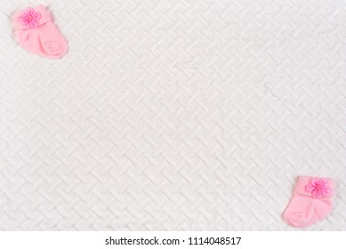 Top view of baby socks for newborn on white blanket. Copy space for text. Top view.