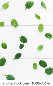 Top view of baby spinach leaves on white wooden background, flat lay