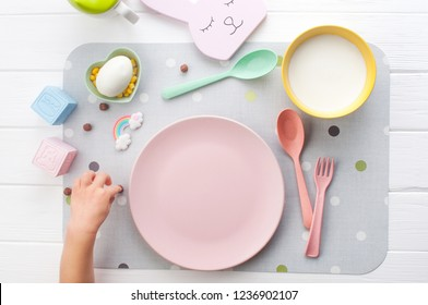Top view of baby waiting for breakfast. Empty pink plate and kid's hand on white wooden background. Flat lay.