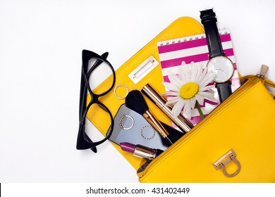 Top view bag with make up female property. Striped notebook, chamomile and cellphone