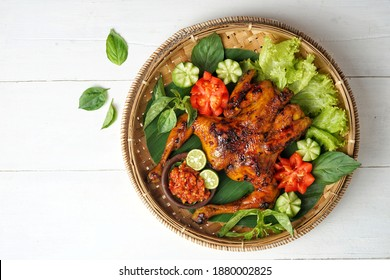 Top view of Bakakak Hayam or Ayam Bekakak or Grilled Whole Chicken with seasonings plus soy sauce, a dish from West Java and Jakarta, Indonesia. Usually served to brides at weddings. Copy space.