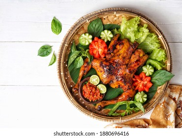 Top view of Bakakak Hayam or Ayam Bekakak, Ayam Bakar is a Grilled Whole Chicken with seasonings plus soy sauce, a dish from West Java and Jakarta, Indonesia. Usually served to brides at wedding.