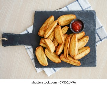 Top view of Baked fried potatoes on black slate plate severed with tomato sauce, Home made Chips wedges country style