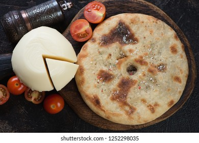Top view of baked ossetian pie with meat stuffing, suluguni cheese and tomatoes, horizontal shot