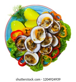 Top view of baked in oven European bittersweet clams served with boiled potatoes, fresh vegetables and greens. Isolated over white background