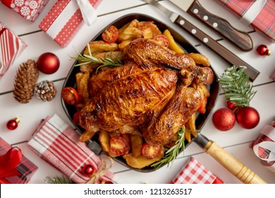 Top view of Baked whole chicken or turkey served in iron square pan with beautiful Christmas decoration around. Placed on white rustical wooden background.