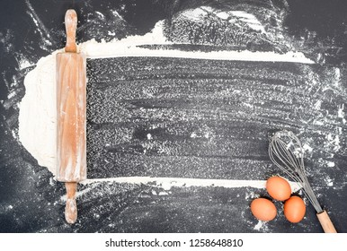 top view baking header on black kitchen table with rolling pin, wheat and eggs