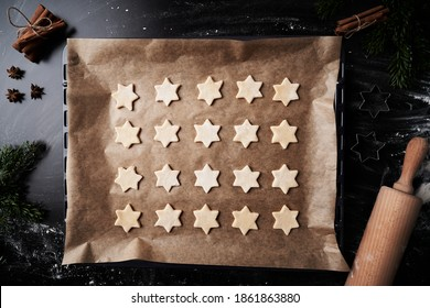 Top view of baking tray with raw star shaped cookies