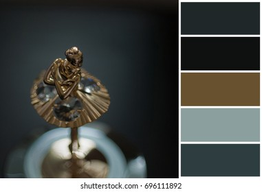 Top view of ballerina statuette on music box. color palette scheme with complementary swatches. Dark photo, grain aded.