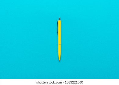 top view of ballpoint pen on the blue background. minimalist flat lay photo of yellow pen over turquoise blue background with central composition