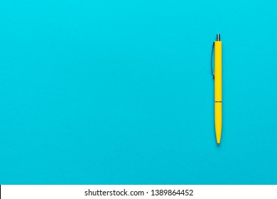 top view of ballpoint pen on the blue background. minimalist flat lay photo of yellow pen over turquoise blue background with copy space