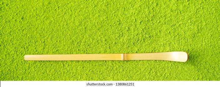 Top view of bamboo Chashaku spoon on powdered Green Matcha tea background with copy space. Long wide banner with copy space.