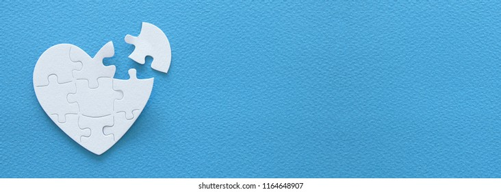 Top view banner of paper white heart puzzle with missing piece over blue background. Health care, donate, world heart day and world health day concept