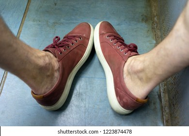 Top view of bare feet in red sneakers on the blue floor. Varicose veins