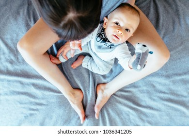 Top view of barefoot mother and son sitting together on bed covered gray blanket. Inquisitive infant baby boy looking up at camera. Dedicate more time for your child concept.