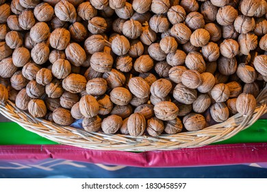 A top view of a basket of unshelled walnuts