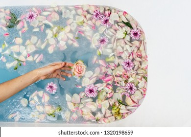 Top view of bath filled with blue bubble water, flowers and petals with woman's hand, spa or selfcare concept