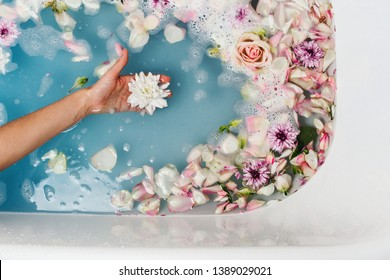 Top view of bath filled with blue bubble water and petals with woman's hand holding flower, spa or selfcare concept