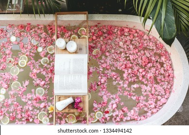 Top view of bath tub with flower petals and lemon slices. Book, candles and beauty product on a tray. Organic spa relaxation in luxury Bali outdoor bathroom.