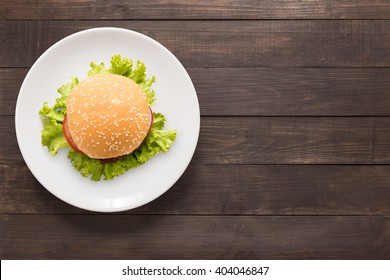 Top view BBQ burger on white dish on wooden background.