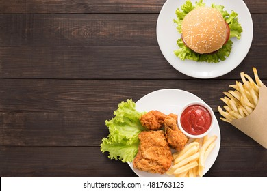 Top view bbq hamburger, french fries and fried chicken on the wooden background. Copy space for your text.