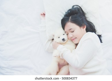 Top view of beautiful asian girl sleeping with siberian husky puppy on  white bed