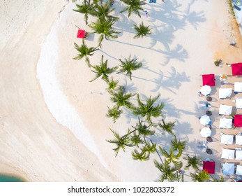 Top view of beautiful  beach with umbrellas and beach chairs and palm trees, aerial drone shot,travel and leisure concept