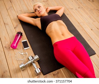 Top view of beautiful blonde sportswoman looking away and lying on yoga mat on wooden floor near dumbbells, smartphone and bottle of water