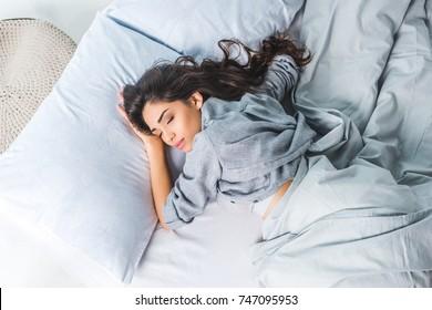 top view of beautiful brunette girl sleeping in bed