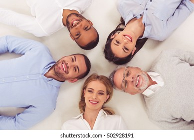 Top view of beautiful business people in smart casual wear looking at camera and smiling, on white background