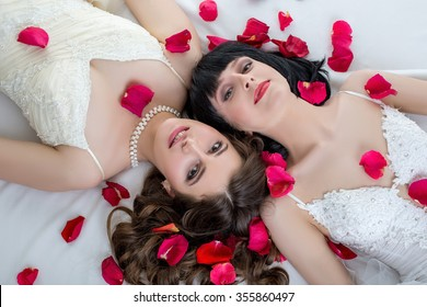 Top view of beautiful dark-haired brides lying