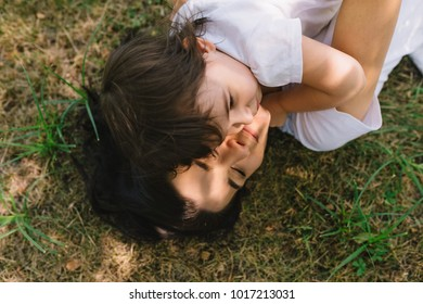 Top view of beautiful happy mother and her little fun smiling daughter playing outdoor. Cute mom and her cheerful child playing in the park together. Portrait of happy family. Motherhood.