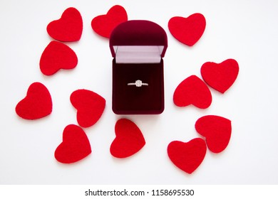 Top view of beautiful luxury wedding ring with precious stone in red velvet gift box on white backgroung with red hearts. Valentine's day marriage proposal. Present and love concept.
