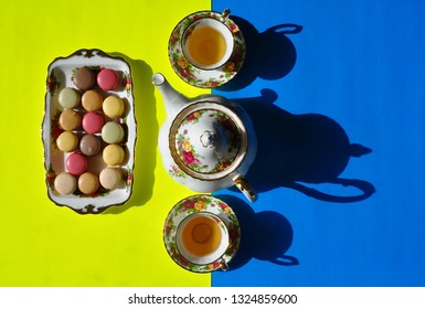 Top view of a beautiful plate with macaroons, a tea pot and tea cups in a yellow and blue backgrounds with shadow