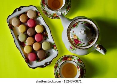 Top view of a beautiful plate with macaroons, a tea pot and tea cups in a yellow background