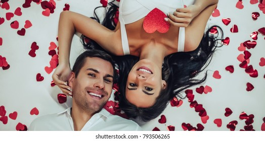 Top view of beautiful romantic couple in love is lying on the floor with many small red hearts nearby. Smiling and looking at camera. Happy Saint Valentine's Day!