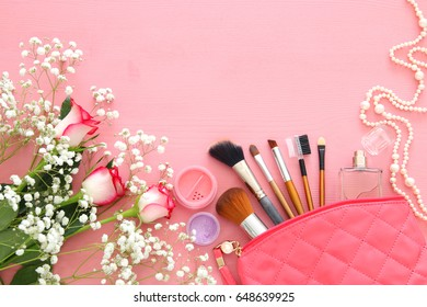 Top view of beautiful roses next to makeup and perfume on wooden background.