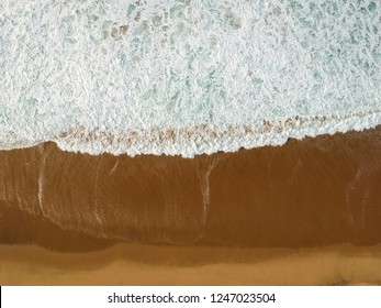 Top view of a beautiful sandy beach aerial shot with the waves rolling into the shore. Drone shot