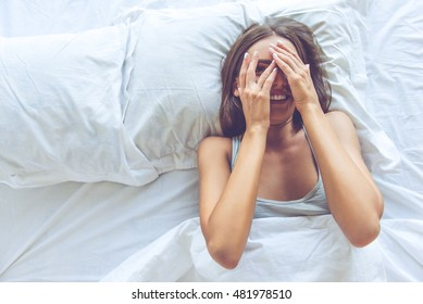 Top view of beautiful sexy young woman covering her eyes, looking at camera and smiling while lying in the bed