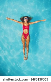 Top view of a beautiful smiling happy young woman enjoying in the water of the pool. She is relaxing and swimming in clear blue water and smiling.