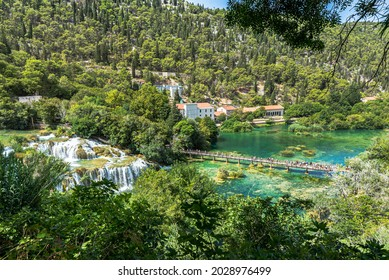 Top view of the beautiful waterfall flowing into the transparent turquoise water lake and tourists enjoying the view at the Krka National park. Croatia 2021