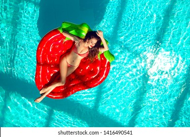 Top view of a beautiful woman enjoying on inflatable red strawberry in swimming pool.  bikini tanned girl model with long hair posing on pool float mattress. Summer vacation.