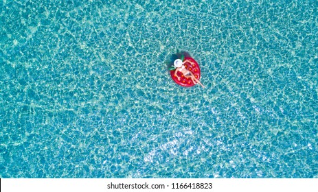 Top view of a beautiful woman with a hat swimming on the inflatable big strawberry in the transparent blue sea. Aerial view of lady relaxing on the floating mattress.