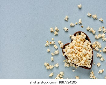 Top view of a beautiful wooden bowl in the form of a heart with popcorn, on a blue background.