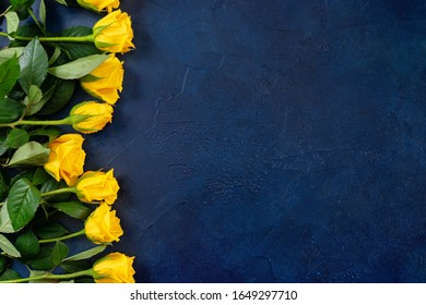 Top view of beautiful yellow roses on dark blue background