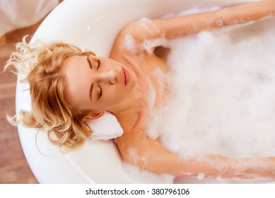 Top view of beautiful young blonde woman enjoying pleasant bath with foam, lying with closed eyes