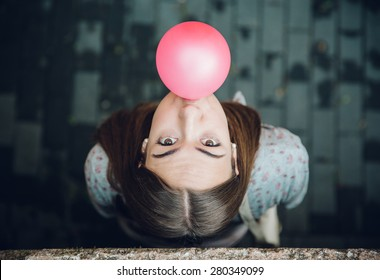 Top view of beautiful young brunette teenage girl blowing pink bubble gum