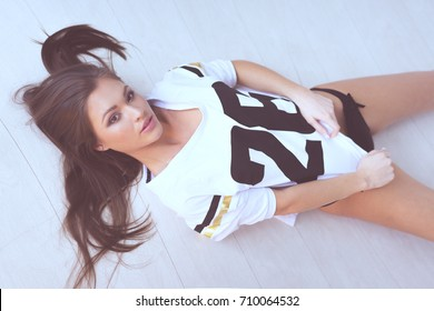 Top view of beautiful young brunette woman wearing sport t-shirt with number 26 and black panties looking at the camera while laying on the light wooden floor