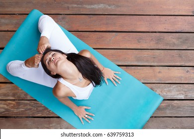 Top view of beautiful young fitness woman working out on wooden floore terrace, doing yoga exercise, full length